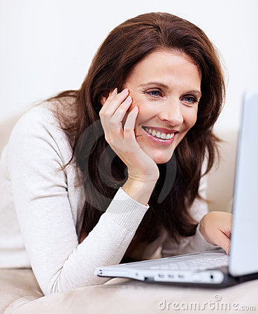 Lovely middle aged woman using laptop at home