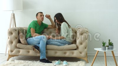 Relaxed couple talking together sitting on sofa stock footage