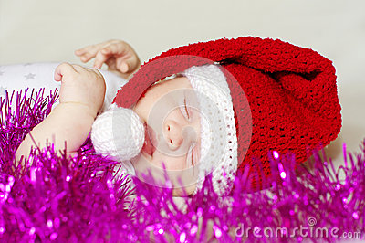 Lovely sleeping baby in New Year s hat among spangle