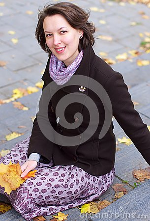 Lovely smiling woman with autumn leaves