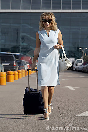 Lovely smiling woman traveling with a suitcase