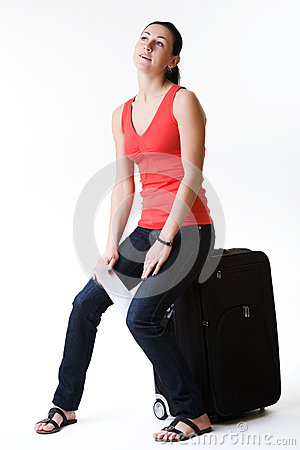 Dreamy woman sitting on a suitcase