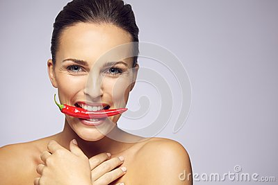 Lovely woman with hot chili pepper in mouth