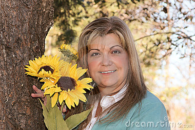 Lovely woman poses holding flowers next to tree