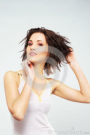 Lovely woman is putting hair her wet hair