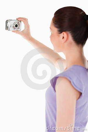 Lovely woman using a camera while standing