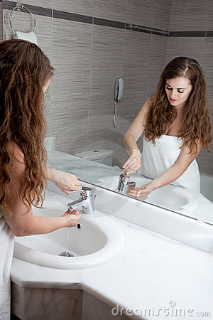 Lovely woman washing hand in bathroom