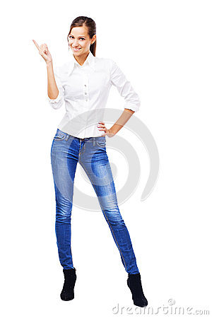 Lovely woman in white shirt and blue jeans pointing at copyspace
