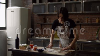 Woman rolling out dough with rolling pin at home stock video