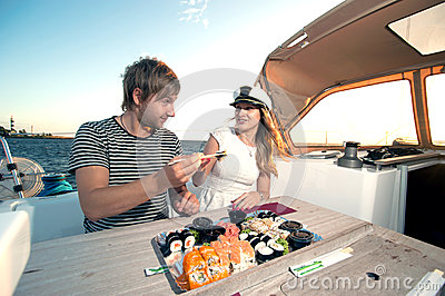 Lovely young couple eating sushi