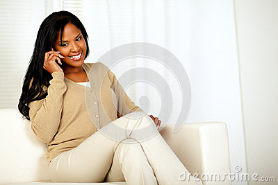 Lovely young woman smiling and conversing on phone