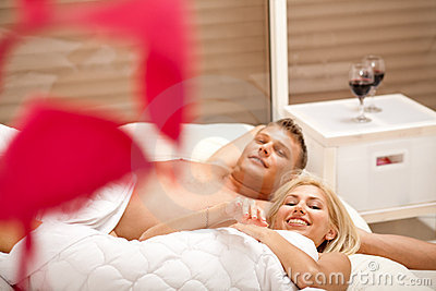 Lovers in bed smiling to camera