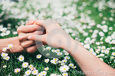 Lovers holding hands on spring flowers field