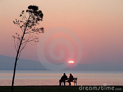 Lovers and sunset from sea