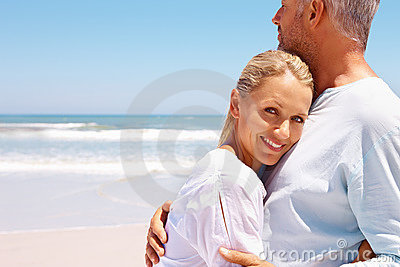 A loving aged couple together at the beach