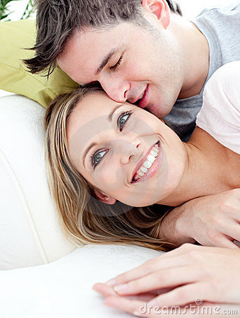 Loving boyfriend hugging his girlfriend on a sofa