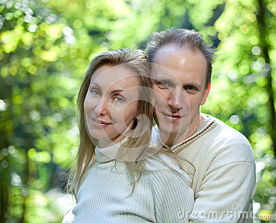 Loving couple on a background of green foliage.Portrait in a sunny day