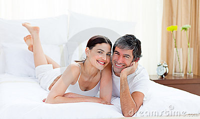 Loving couple cuddling lying on their bed