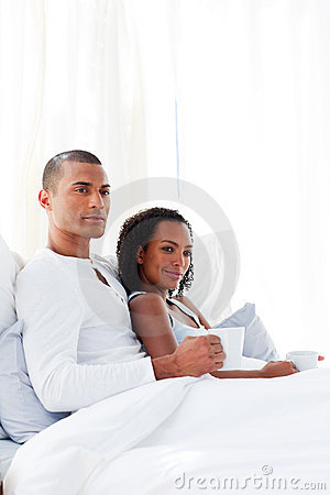 Loving couple drinking a coffee on their bed