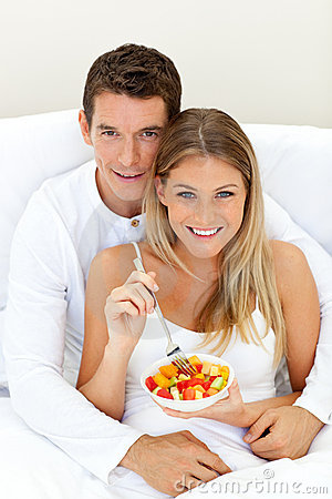 Loving couple eating fruit lying on their bed