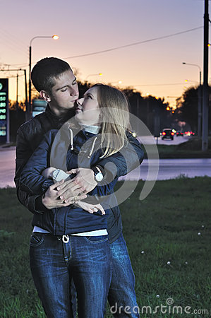 Loving couple embraces in the evening