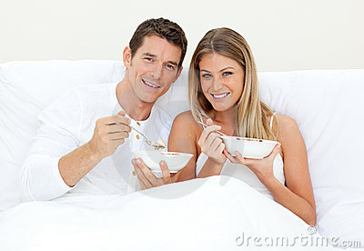 Loving couple having breakfast lying on their bed