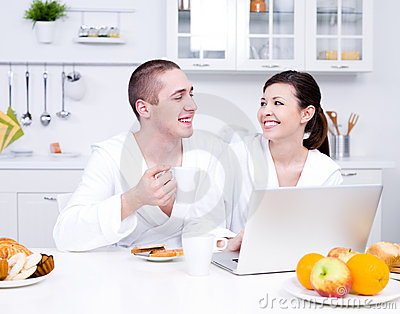 Loving couple with laptop in the kitchen