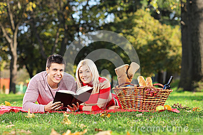 A loving couple reading a book in a park