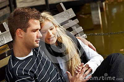 Loving couple resting on bench in park