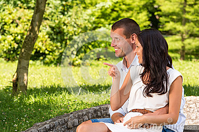 Loving couple sitting and laughing in park