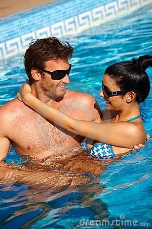 Loving couple in swimming pool smiling