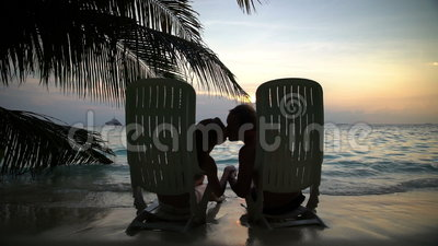 Loving couple on the tropical beach are admiring the sunset and kissing. Slow motion. Loving couple on a tropical beach are admiring the sunset and kissing stock footage