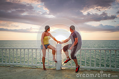 Loving couple watching sunset at the sea