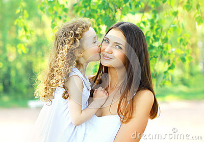 Loving daughter kissing mother, happy young mom and child in warm sunny summer day on the nature Stock Photo