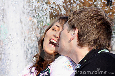 Loving(enamoured) couple kisses against a fountain