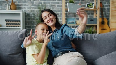 Loving mom taking selfie with adorable son using smartphone camera hugging child. Showing thumbs-up and v-sign hand gestures smiling feeling love. People and stock video