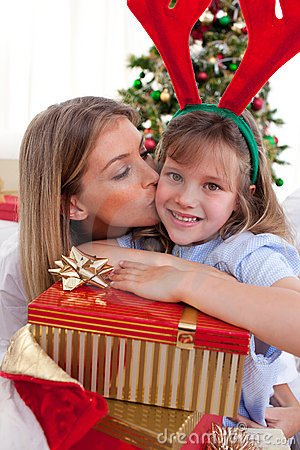 Loving mother kisses daughter at Christmas