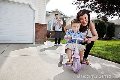 Loving Mother Teaching Son To Ride Tricycle