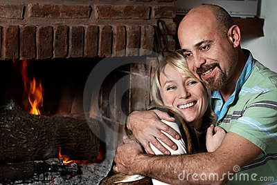 Loving pair near a fireplace in winter evening