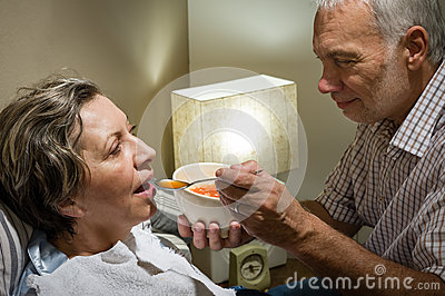 Loving retired husband feeding his ill wife
