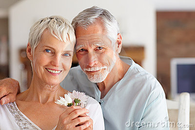 Loving senior couple holding a flower at home
