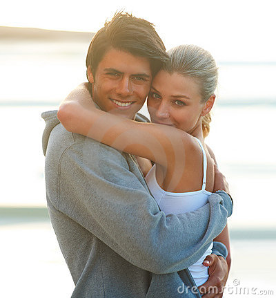 Loving young couple hugging eachother on the beach