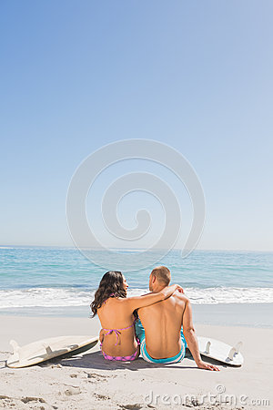 Loving young couple sitting with their surfboards