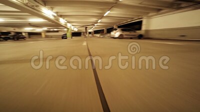 Car driving inside of parking garage stock video footage