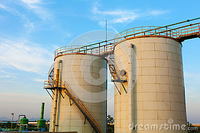 Low-angle shot of ladder and tanks refinery.