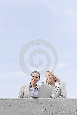 Low angle view of happy young businesswomen with laptop looking away while standing on terrace against sky