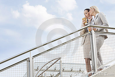 Low angle view of young businesswomen with disposable coffee cups looking away while standing by railing against sky