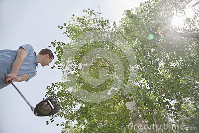 Low angle view of young man getting ready to hit the golf ball on the golf course, lens flare