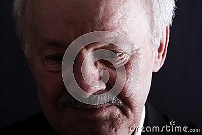 Low key portrait of depressed senior man