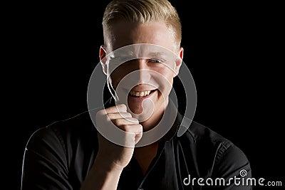 Low key portrait of joyous man looking straight.